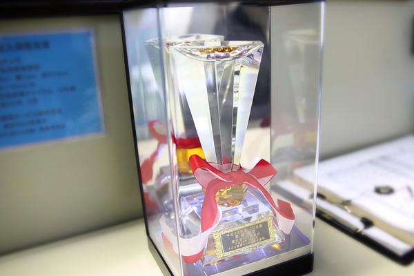 オフィスの片隅には<br /> 「CS活動 最優秀賞」のトロフィー。<br /> よく見ると<br /> LEDの電飾が仕込まれていてキラキラ。<br /> 聞けばこれも自作だそうです。
