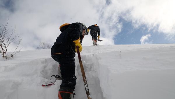 雪の壁に足場を掘りながら登る現場も